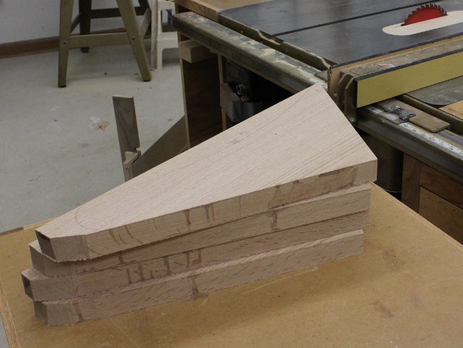 Four pew arm blanks are veneered and stacked