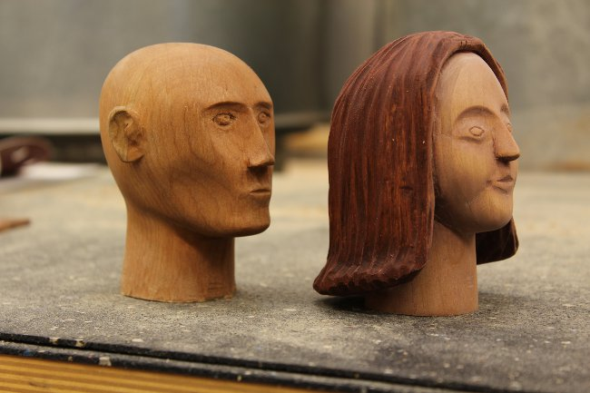 Viewinf two carved wooden heads side by side
